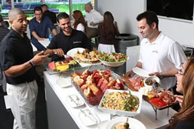 Photo of Fans Enjoying Food in Luxury Suite